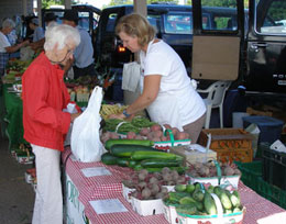 Produce vendor serving an elderly customer at the Market